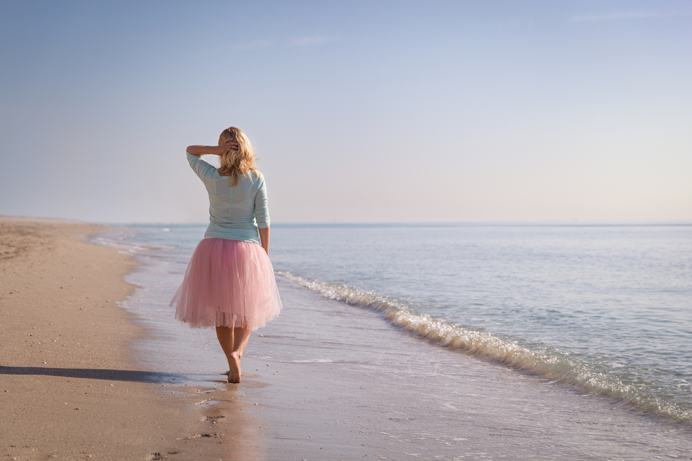 woman walking along beach alone