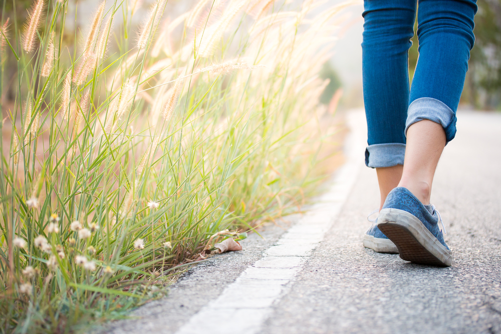 care for your wellbeing  by getting outside - woman's feet walking on path next to grass